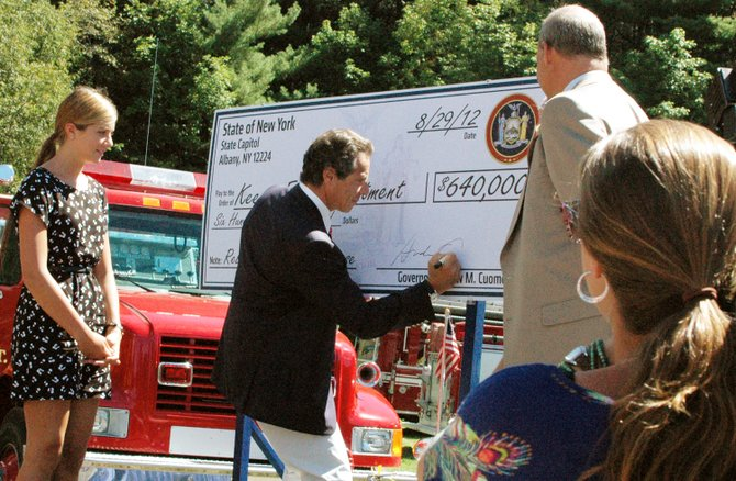New York State Gov. Andrew Cuomo signs a check for $640,000 to the Town of Keene to help fund their firehouse project.