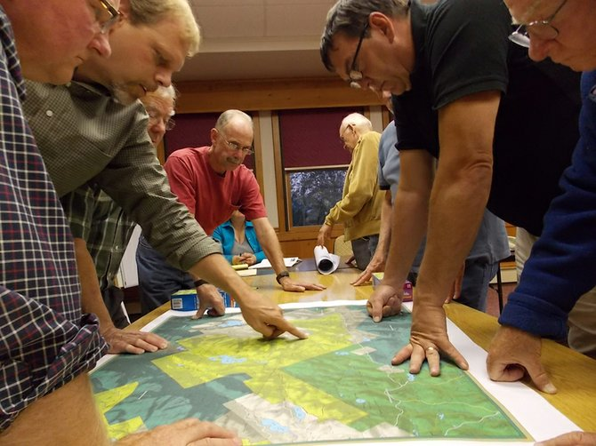Clockwise from left, NYSDEC Region 5 Director Robert Stegeman, DEC Regional Forester Kris Alberga, Minerva Town Board members Eric Klippel and Stephen McNally, and a few citizens survey a map showing the upcoming state land purchase in the town that were discussed during the Aug. 29 meeting.