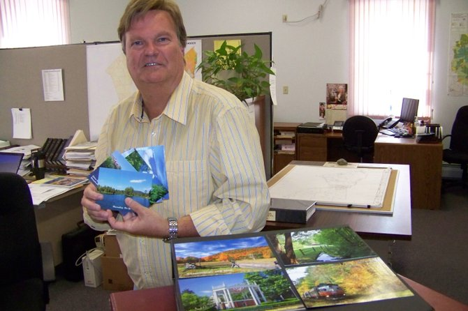 Warrensburg Town Assessor Greg Klingler poses with some of the post cards depicting Warrensburg scenes  that he's recently published.  Local citizens say the last time anyone published contemporary scenes of Warrensburg was likely as far back as the 1960s or early 1970s.
