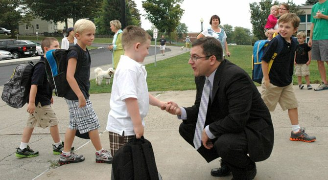 """New Waterman Principal Gary Gerst got down to eye level and greeted students as they got off the buses for the first day of school.  """"How are you doing?!""""  he asked enthusiastically, asking for high fives."""