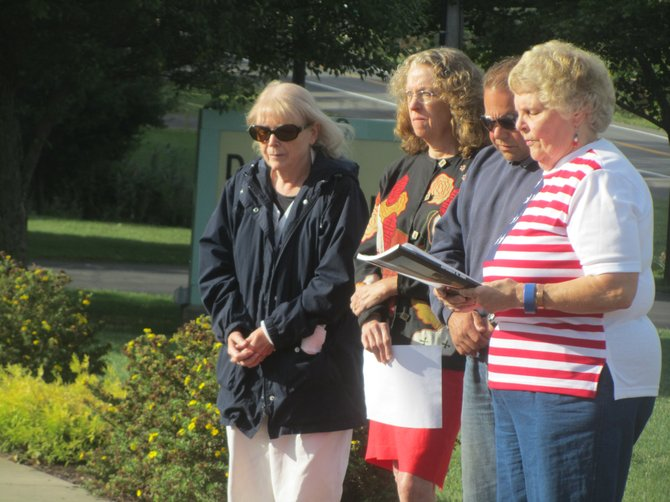 Elaine Lostumbo, far right, led a small remembrance ceremony at the 9/11 memorial in DeWitt this morning.