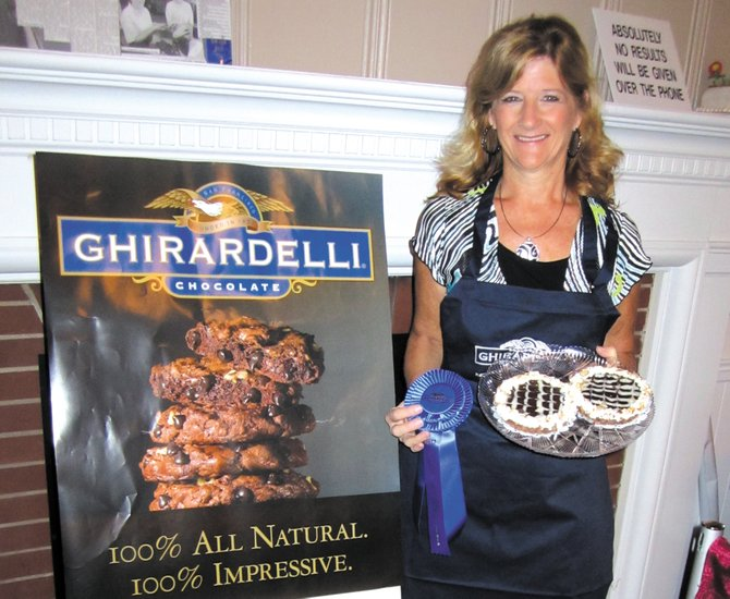 Elaine Reilley, of Jordan, holds up her award-winning Almond Joy Tarts in one hand and her blue ribbon in the other.