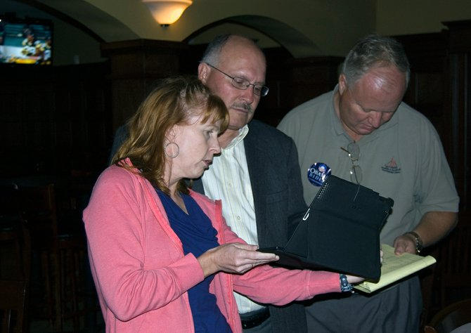 Niskayuna Councilwoman Julie McDonnell holds up her iPad so Town Supervisor Joe Landry, running in the 110th Assembly District Democratic Primary, can see election results. Landry failed to capture the ballot line to Philip Steck, a four-term Albany County Legislator.