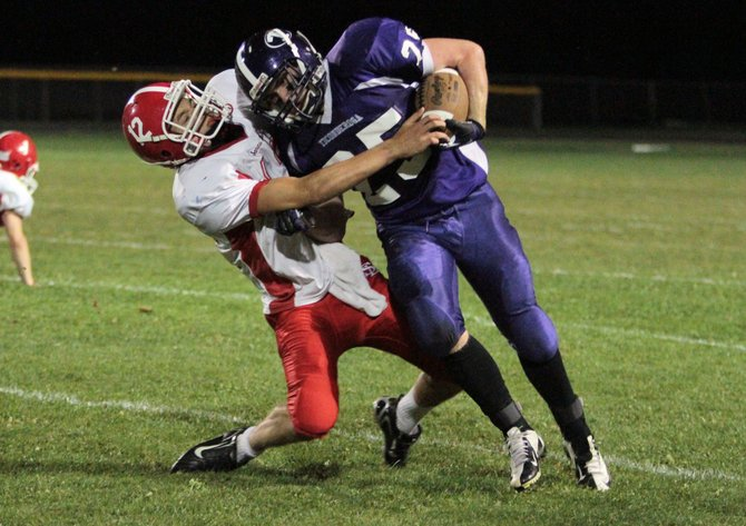 Ticonderoga's Tanner Wright powers through a tackle by Saranac Lake's Kevin Morgan in Champlain Valley Athletic Conference football action Sept. 14. Saranac Lake won, 30-6.