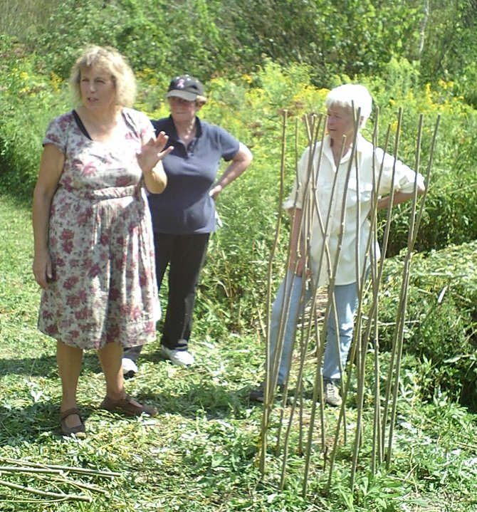 Traditional basket weaver Bonnie Gale helps two willow weaving workshop participants complete their willow pea-cage trellises on Aug. 25.