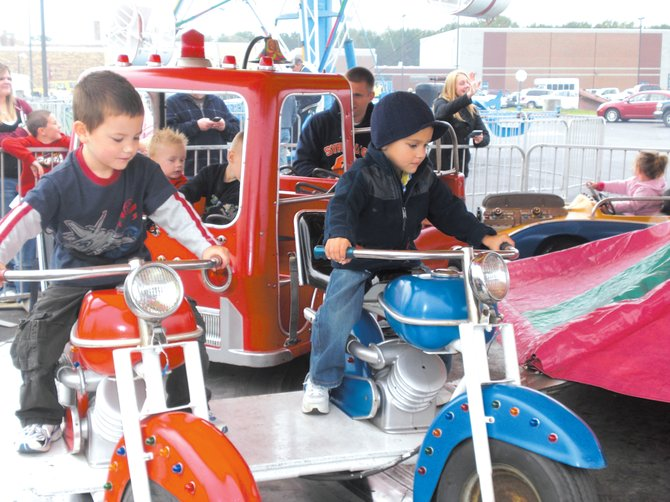 Carson Vasile, 3, (right) and Carson Bell, 5, enjoy one of the rides at the Jordan Fall Festival last year. This year's festival is set to take over Beaver Street Friday through Sunday.