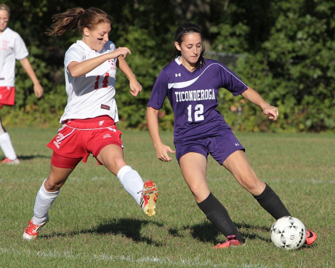 Ticonderoga's Andrea Rich heads up field as Moriah's Sarah Slattery defends in Northern Soccer League girls play Sept. 19. Rich scored both goals as Ti won, 2-1.