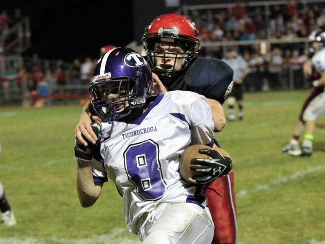 Ticonderoga's Ty Denno is tackled by Moriah's Tyler Pratt as the Sentinels downed archrival Moriah, 18-12, in Champlain Valley Athletic Conference football action Sept. 21.