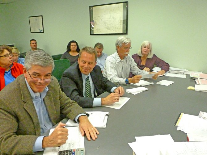 Absentee ballots were counted in the Democratic primary race between candidates John Cunningham, sitting far left, and Bill Reinhardt, sitting second from right, on Monday, Sept. 24. Reinhardt officially won the election by approximately 30 votes and will face Republican Jeremy Martelle in November.