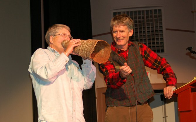 Beth Petrie, of Indian Lake, attempts to call a moose while Ed Kanze holds the microphone during the Great Adirondack Moose Festival moose-calling contest Saturday, Sept. 22 at the Indian Lake Theater.