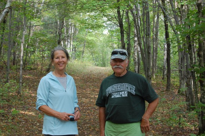 Hal Moore and Libby Yokum stand on the New Land Trust in Saranac which consists of 287 acres, 10-12 miles of trails for hiking, snowshoeing and cross country skiing, a meadow and stage for music and a large stone labyrinth.