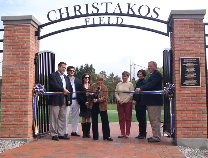 Members of the Christakos family gather around their matriarch, Harriet Christakos, as she cuts the ceremonial ribbon to Christakos Field, named in honor of her late husband Nicholas, on Sept. 29 at Cazenovia College.