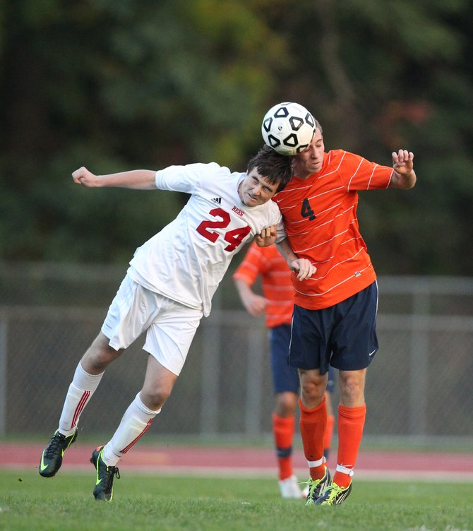 Baldwinsville freshman midfielder Evan Ingersoll (24) leans in with his head as Liverpool's Michael Egan (4) also tries to make contact with the ball in Tuesday night's game.