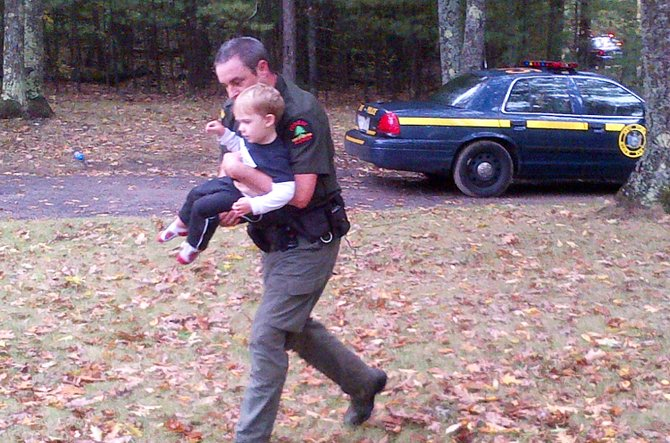 A DEC Forest Ranger carrying the two year old boy shortly after he had been located by local residences.