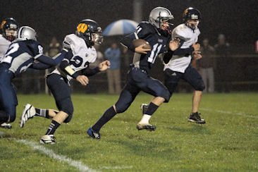 Chased by Warrensburg defenders, Lake George running back Willy Blunt takes off downfield during a football game held Saturday Sept. 29 in Lake George. The Warriors beat the Burghers 20-14 in a comeback vitory, and Blunt was credited with giving his team several key first downs as well as scoring two touchdowns.