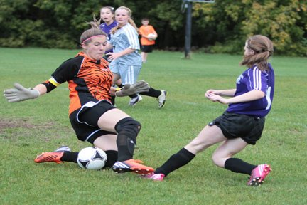 Crown Point goalie Amanda Wolf makes a sliding save against Minerva-Newcomb's Makenzie Winslow during Northern Soccer League girls play Oct. 1. Minerva-Newcomb won, 5-0.