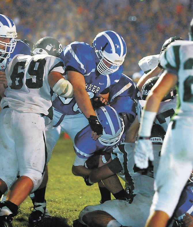 Shaker quarterback Chris Landers plunges into the end zone for the first touchdown of Fridays game against Shenendehowa in Latham. Landers added another touchdown in the second quarter to help the Blue Bison defeat the Plainsmen 35-8 in front of 3,000 people.