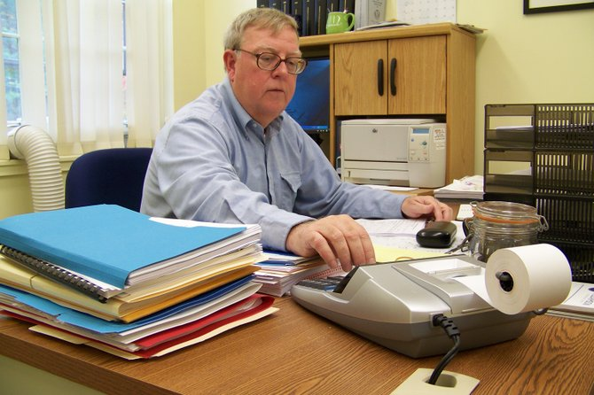 Delving into budgetary details, Warrensburg Town Supervisor Kevin Geraghty punches the keys on his desk calculator Thursday Oct. 4 in his office in the Emerson Town Hall.