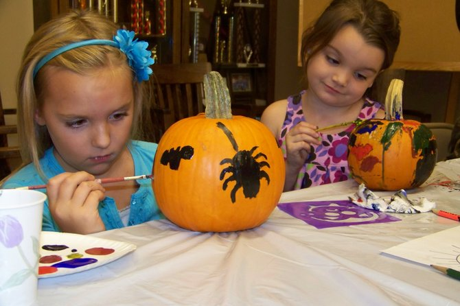 Isabella Lewis, 8  (left) and Kasey Baker, 5 — both of Brant Lake — paint pumpkins at a craft activity held Saturday in conjunction with the Great Brant Lake Duck Race — a beloved local community tradition. Craft session supervisor Maureen Robinson said the community was indebted to Chuck and Cindy Hilton and Danny Wolke  for their donations of six dozen pumpkins  for area children to paint and take home. Wolke also donated a massive 250-pound pumpkin that was to serve as a decoration at the event, but was left near the town ballfield because it was too heavy to move.