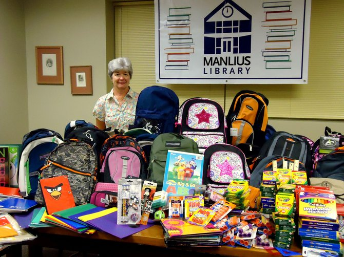Pam Burrows, Manlius Library Bookmark Café manager, organizes school supplies to be donated to local schools.