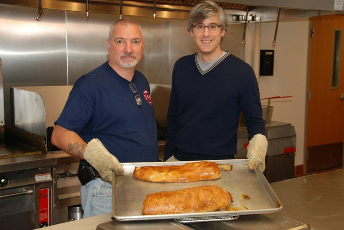 "Christopher Massie, left, and Cooking Channel host Mo Rocca make Italian Garbage Bread at Elsmere Fire Station as part of Massie's appearance on the show ""My Grandmother's Raviolis."""