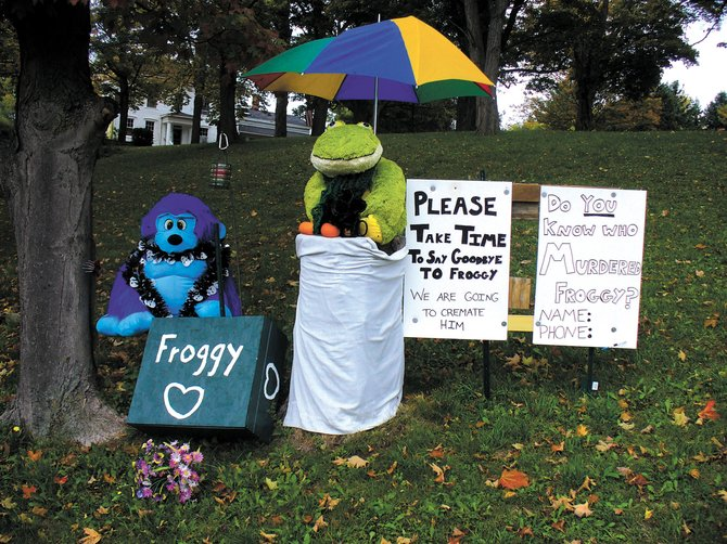 A plush blue gorilla, a stuffed frog named Francis and a box containing Froggy's remains now mark the former home of Froggy, Marcellus' festive frog, on North Street.