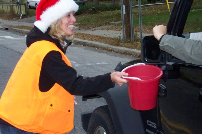 Angela Davis of Warrensburg collects money in a coin drop held Saturday to benefit Operation Santa Claus, which provides clothing and food for needy area families during the holidays. The charity is holding its annual Gift Baskets Galore fundraiser this Sunday at Warrensburg Central School, and the community is invited to participate.
