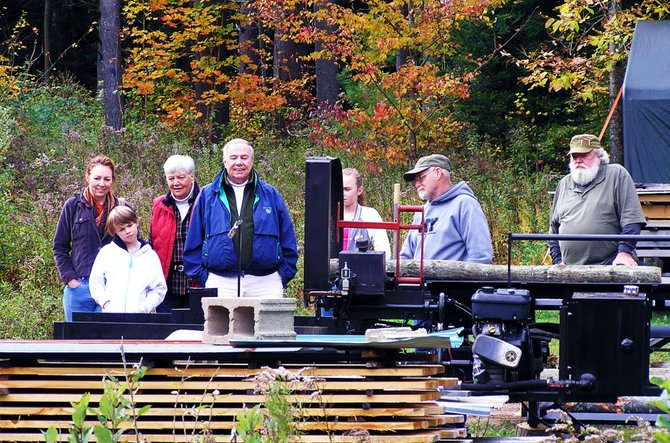 Marvin 'Pinky' O'Dell (second from right) demonstrates an automated firewood processing machine at Martin's Lumber during this last weekend's Thurman Fall Farm Tour. The machine cuts and splits logs for use in wood stoves or fireplaces.