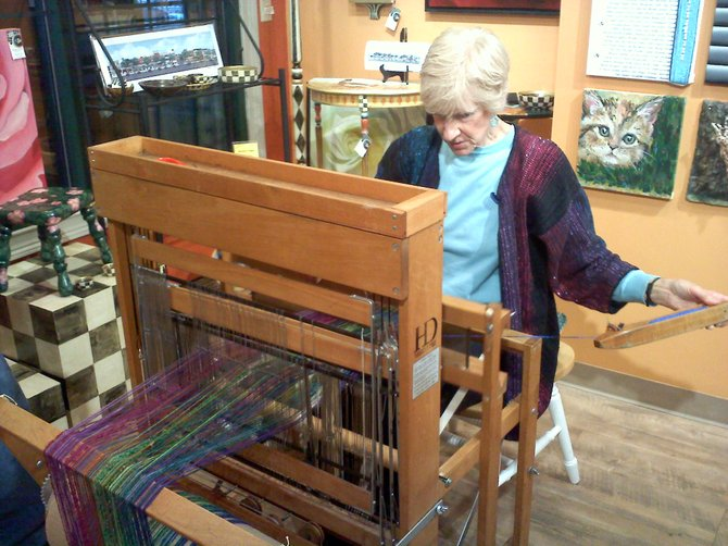 Barbara Decker demonstrates weaving on her loom, as she makes a scarf on Oct. 6 at Cazenovia Artisans.