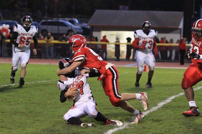 Baldwinsville junior defensive tackle Justin Weeks (92) tackles Utica Proctor quarterback Jordan Treen in Friday night's game. This play knocked Treen out of the game, and the Bees went on to a 40-32 victory over the Raiders.
