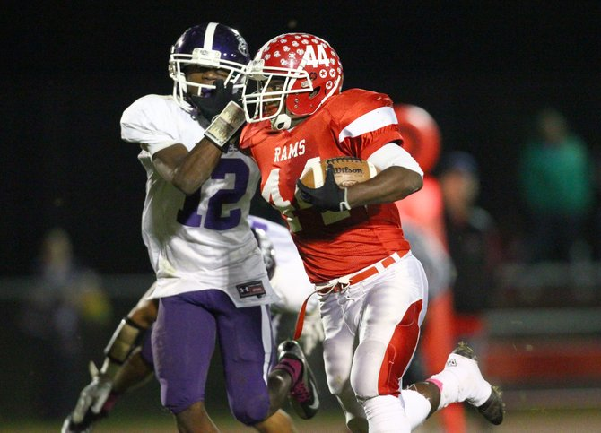 Jamesville-DeWitt running back Rasheed Baker (44) uses a stiff arm to fend off Watertown's Shyheim Gadson (12) in Thursday night's Class A playoff game. Baker ran for 164 yards on 20 carries in the Red Rams' 49-0 victory over the Cyclones.