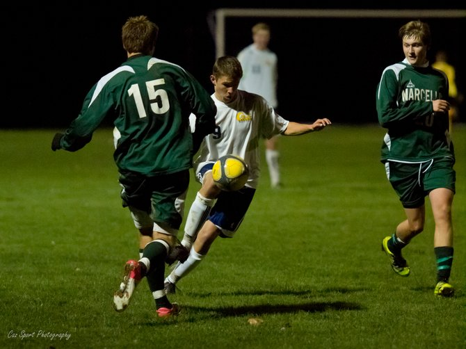 Cazenovia varsity soccer player Peter Burr navigates the ball between two Marcellus defenders during the game on Oct. 16 at the Sean Googin Sports Complex in Cazenovia. The Lakers won the match against the Mustangs 2-1 in overtime.