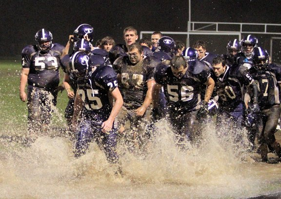 The Ticonderoga football runs to its bench during its 26-14 victory against AuSable Valley Oct. 19. The game was played in driving rain and mud.
