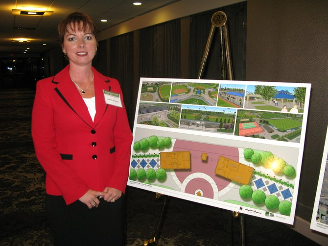 Syracuse Challengers parent volunteer Jennifer Savastino stands with site plans for the athletic complex that will house the baseball league.