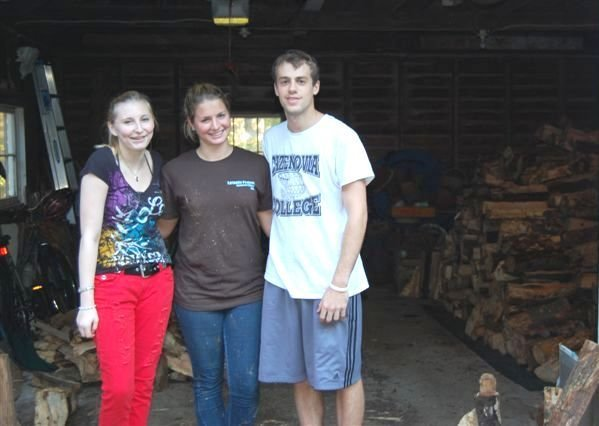 "Cazenovia College students Sally Taylor, left, Hilary Hext and Nick Bartolotta pause for a photo while stacking six cords of wood for an area senior during CRIS's ""Lend A Hand Week,"" the first week of October."