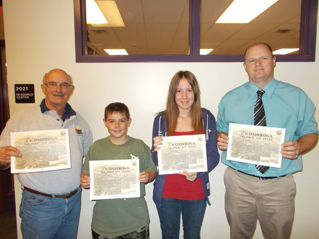 Ticonderoga Middle School students are helping the First 250 Year Committee sell 2013 historical calendars. From left are Bob Dedrick of the committee, student Lucas Grinnell, student Sierra Stacy and teacher Kyle Lang.