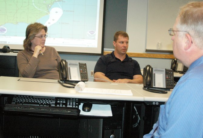 Patty Bashaw, Michael Blaise and Don Jaquish listen during a conference call Oct. 26 in preparation of the approaching &quot;Frankenstorm,&quot; a combination of Hurricane Sandy and an arctic front that could hit the area late Monday evening into Tuesday.
