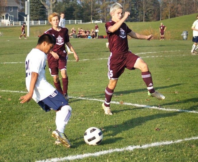 Cazenovia varsity soccer player Kevin Porter avoids Sherburne-Earlville defenders and crosses the ball for his Laker teammates on Oct. 26.