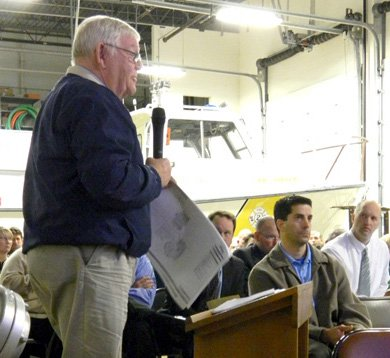 Don Rhuda, of Musco Lighting Company, explains the proposed 70-foot field lighting for the Victory Sports Medicine athletic complex at the Oct. 16 Zoning Board of Appeals public hearing. VSM owner Dr. Marc P. Pietropaoli, seated behind podium, listens.