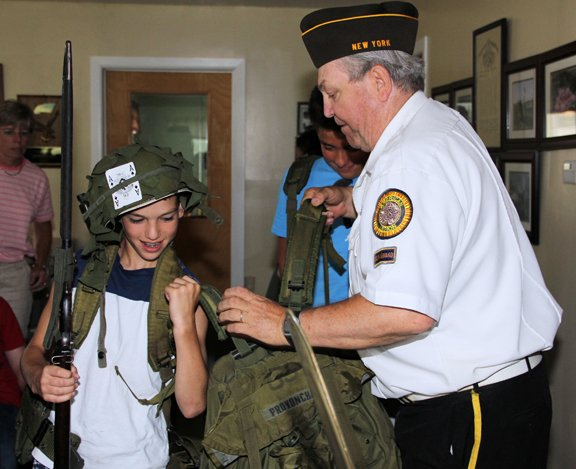 A  student at Ticonderoga Elementary School learns what it's like to be a soldier from Tom Provoncha of the Ticonderoga Veterans of Foreign Wars.  Each year Provoncha spends a day with Ti students explaining military equipment and history as he emphasizes the role of veterans.