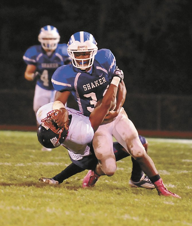 Shaker's Kenny Jackson pushes aside a Schenectady defender during last Friday's Section II Class AA semifinal game in Latham. Jackson rushed for 95 yards and a touchdown in the 28-21 win.