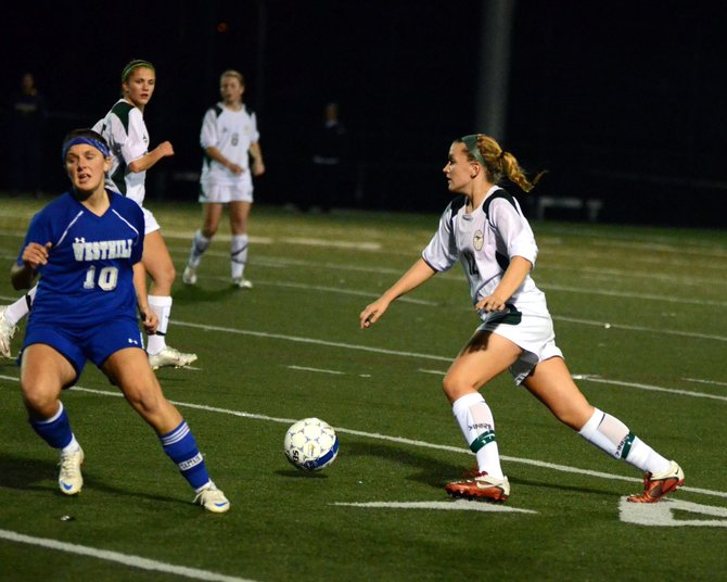 Marcellus senior defender Meghan Witkowski (12) dribbles past Westhill's Maggie Tripodi (10) in Tuesday night's Class B semifinal. Witkowski and her fellow Mustang defenders helped contain the Warriors throughout last Tuesday night's 2-0 win, not allowing a direct shot on the net.