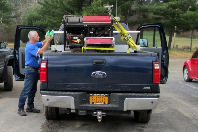 Jay DPW Director Chris Garrow secures town generators to the back of a truck as he prepares to transport them to New York City to help with Hurricane Sandy relief efforts.