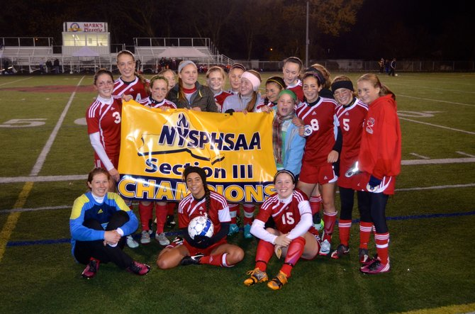 Jamesville-DeWitt's girls soccer team with the Section III Class A championship banner after defeating Whitesboro 1-0 in Thursday night's title game at Chittenango High School. It's the Red Rams' fourth consecutive sectional title, and the third straight it has won by topping the Warriors in the finals.