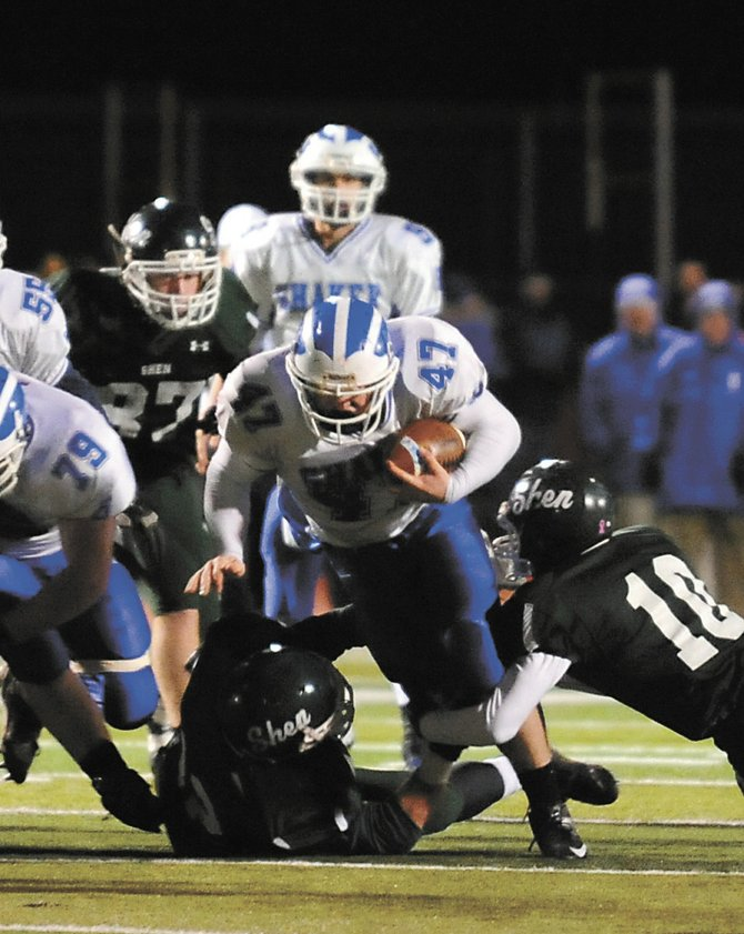 Shaker's Ryan Griffin tries to get through a pair of Shenendehowa defenders during last Friday's Section II Class AA championship game in Clifton Park. Griffin rushed for 122 yards and a touchdown to lead the Blue Bison to a 14-0 win.