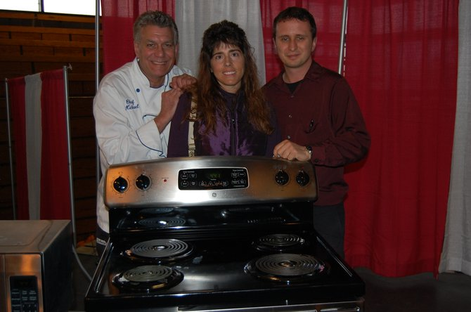 Sheri Provost won a new range, the grand prize at the Taste of Home. On the left is Culinary Specialist Michael Barna, and on the right is the event's emcee, Shaun Kittle.