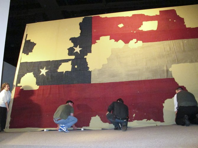 Workers install a massive Confederate flag at the state museum in Albany. Saratoga County native Elmer Ellsworth was killed after he tore down the flag. He was the first Union officer to die in the Civil War.