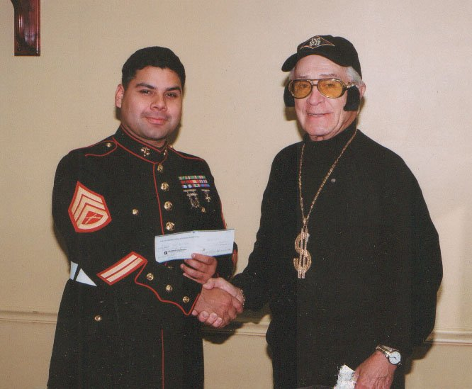 Martin Slagel, right, of the SGC Kiwanis Club, presents a $600 check to Roberto Corona of Marine Toys for Tots.