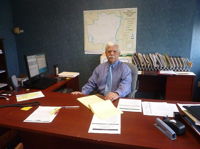 Alan McCartney sits at his new desk at the RCS District office in Ravena. 