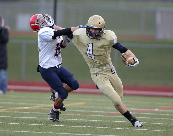 Skaneateles wide receiver Jake Cooney (4) gives a stiff arm to Chenango Forks' Nick Cannon (21) and still hangs on to the ball in Saturday's Class C regional final. Despite Cooney's 12 catches for 144 yards and a touchdown, the Lakers lost, 28-21, to the Blue Devils.